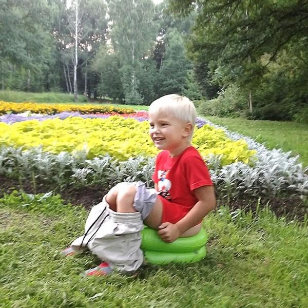 ребенок сидит на надувном горшке Baby-Krug